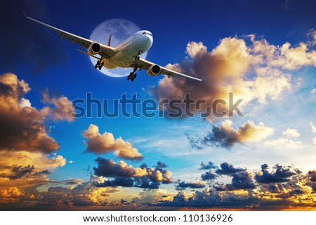 Jet aircraft after take off  in a spectacular sunset sky - stock photo