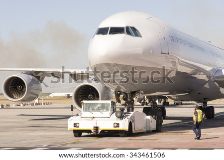 JET AIRCRAFT BEING TOWED BY A TRACTOR AT CAPE TOWN AIRPORT - FEBRUARY 2015 - Passenger jet being moved by a aeronautical tug - stock photo