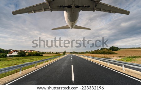 jet aircraft flying low over dual carriageway - stock photo