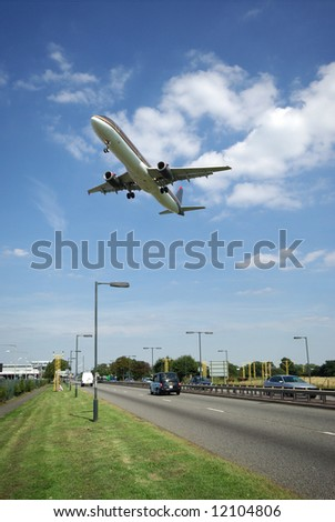 Jet aircraft on landing approach flying low over dual carriageway - stock photo
