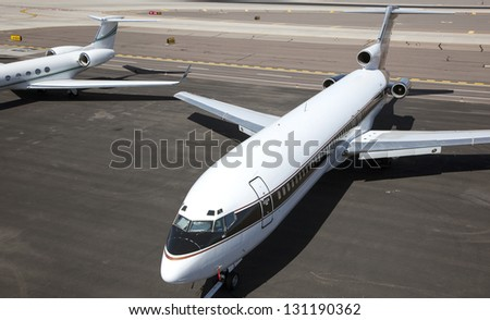 Jet aircraft parked on tarmac at airport - stock photo