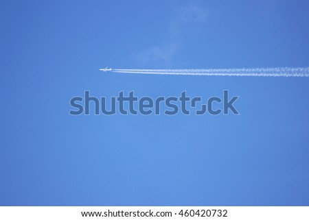 jet aircraft with a white track flying in the blue sky