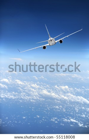 Jet airliner in flight with clouds in the distance - stock photo