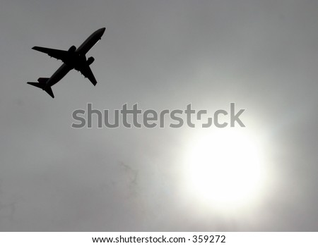 Jet Airplane flying by the cloud curtained sun - stock photo