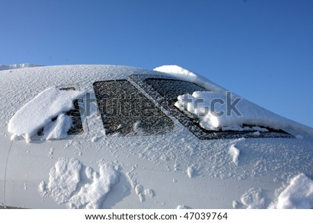 Jet covered in morning snow - stock photo