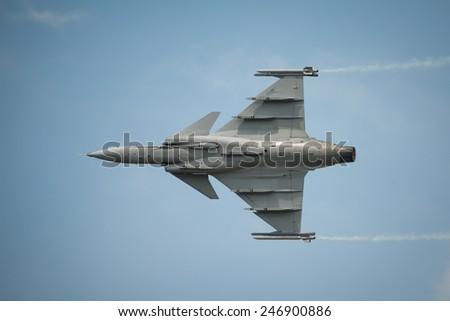 Jet fighter in flight, in blue sky. - stock photo