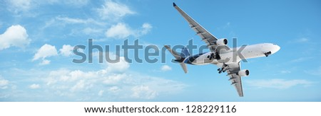 Jet in a blue cloudy sky. Panoramic composition. - stock photo