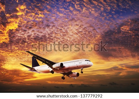 Jet is maneuvering in spectacular sunset sky - stock photo