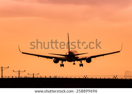 Jet Landing on an Airport Runway at Sunset - stock photo