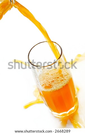 Jet of cold orange juice spills by a glass-impatience to satisfy thirst - stock photo