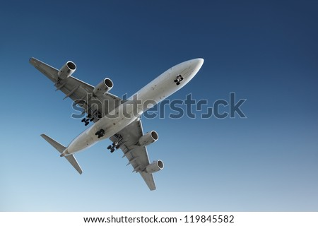 Jet plane flying in blue sky, preparing for landing. - stock photo
