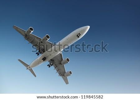 Jet plane flying in blue sky, preparing for landing. - stock photo