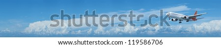 Jet plane in a blue cloudy sky is maneuvering for landing. Panoramic composition. - stock photo