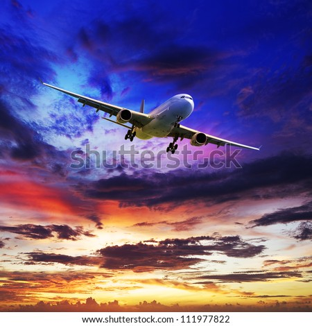 Jet plane is maneuvering for landing in a spectacular sunset sky. Square composition. - stock photo