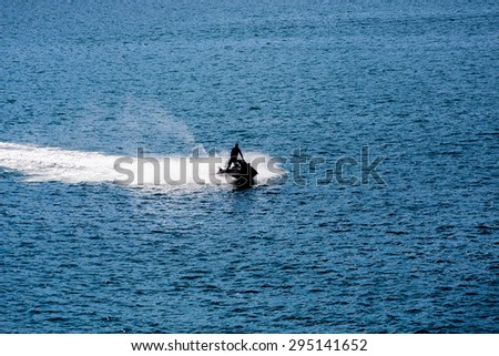 Jet Ski Sillouette on Blue water of calm bay - stock photo