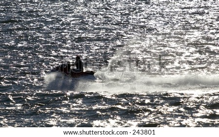 Jet skiers riding across the water - stock photo