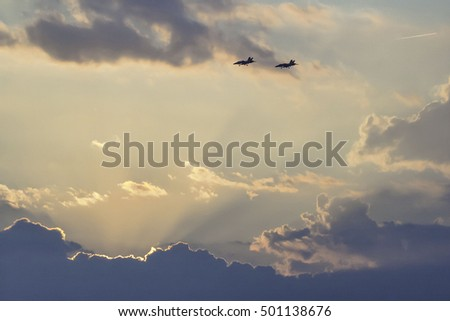 Jets flying over sun-rimmed cumulus clouds with rays and contrail.