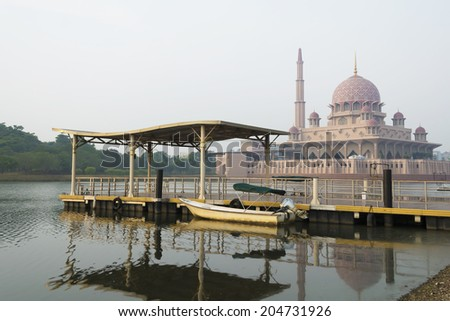 Jetty and boat with Putrajaya mosque background in morning mist - stock photo