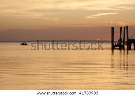 Jetty & boat at sunset - stock photo