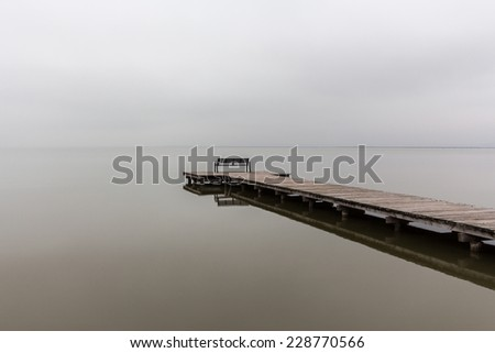 Jetty in foggy weather with bench at end (diagonal) - stock photo