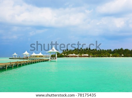 Jetty on a tropical beach - Maldives travel background - stock photo