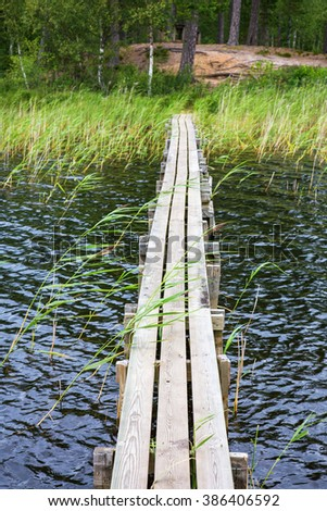Jetty over the water to the beach at the forest - stock photo