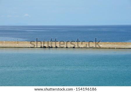 Jetty wall sea and sky horizon abstract background. - stock photo
