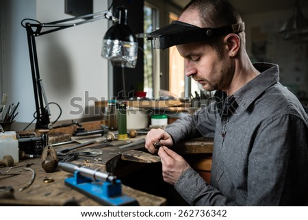 Jeweler working on wedding gold ring in his workshop. Craft jewelery making. - stock photo
