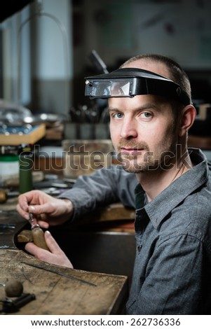 Jeweler working on wedding gold ring in his workshop looking at the camera. Craft jewelery making. - stock photo