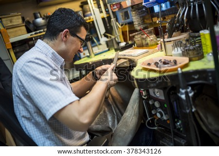 Jeweler working on workbench with many tools - stock photo