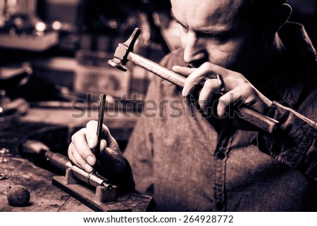 Jeweler working with the hammer on wedding gold ring in his workshop. Craft jewelery making. Monochrome cream tone. Black and white photography. - stock photo