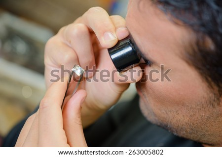 Jeweller appraising a ring - stock photo