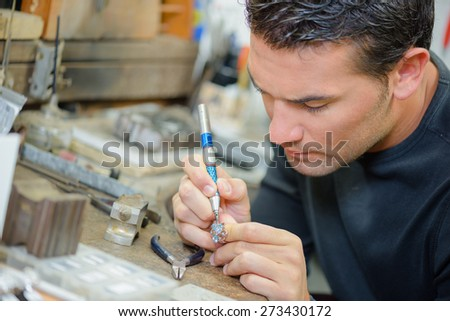 Jeweller hard at work - stock photo