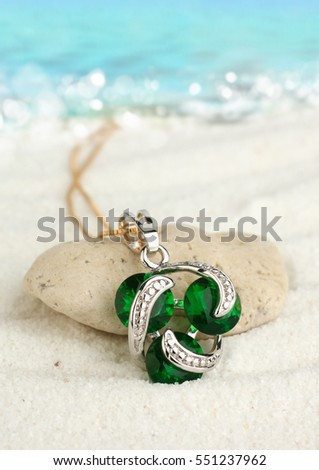 Jewellery pendant with emeralds on sand beach, soft focus
