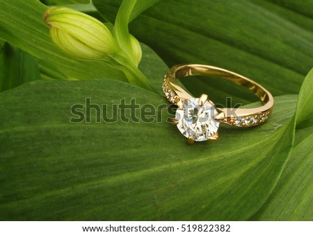Jewellry ring with big diamond on green leafs background
