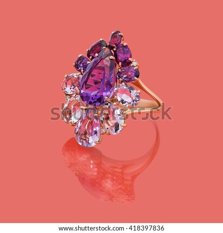 Jewelry gold ring with pink and purple topazes on red background - stock photo