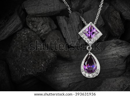 jewelry pendant witht gems on dark coal background - stock photo