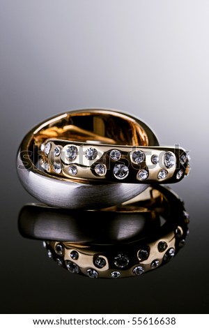 Jewelry photography. Gold ring with Diamonds and silver ring on gradient reflective surface. - stock photo
