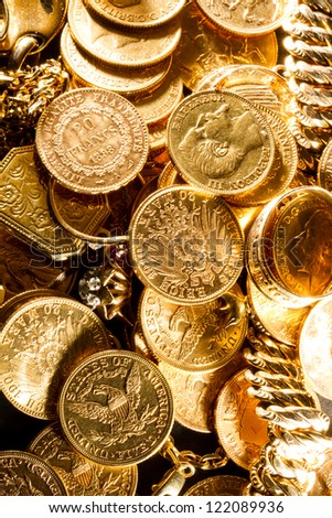 Jewels and gold coins over dark background - stock photo
