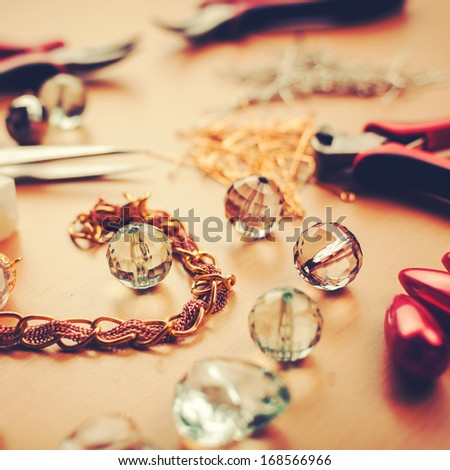 Jewels and tools on jewelers table - stock photo