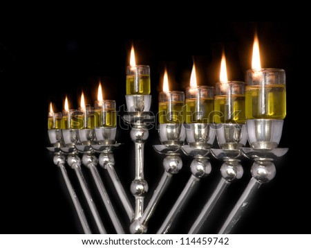 Jewish holiday Chanukah oil menorah. Traditional Chanukah menorah lit with olive oil in glass cups, isolated on a black background. All lights are lit for the eight nights of Chanukah; angled view. - stock photo