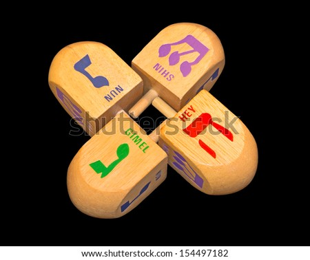 Jewish holiday colorful Chanukah dreidels. Group of large wood dreidels isolated on a black background. Bright green, blue, red, purple color Hebrew letters gimmel, nun, hey, shin.  - stock photo