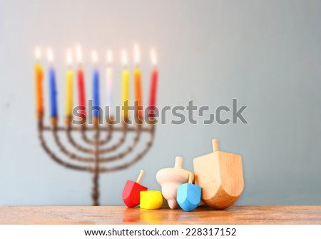 jewish holiday Hanukkah with menorah with wooden dreidels (spinning top).  - stock photo