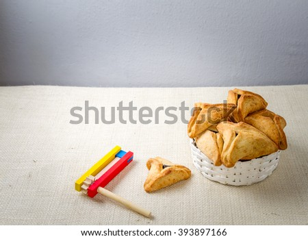 Jewish holiday of Purim. Hamantaschen cookies,  and wooden gragger, free space for text - stock photo