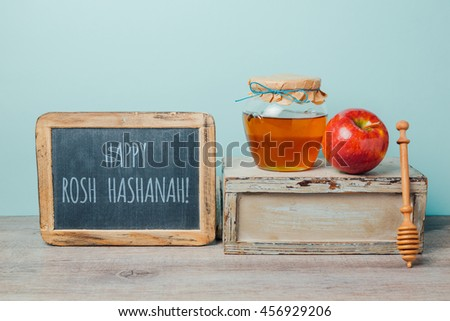 Jewish holiday Rosh Hashana background with chalkboard, honey jar and apple on wooden table