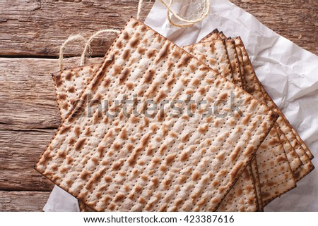Jewish kosher matzo for Passover closeup on a wooden table. horizontal view from above - stock photo