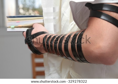 Jewish Man wrapped in tefillin pray . A religious orthodox Jew with arm-tefillin on his left hand prays - stock photo