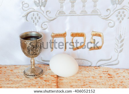 Jewish Passover traditional food: matzoh -  Jewish unleavened bread  bread for Passover, wine cup and egg. Hebrew text - Pesah - translation refers to ritual ceremonies during Passover