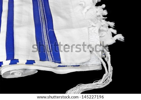 Jewish Prayer shawl, tallit.White wool cloth garment with knots and fringes worn by Jewish men during prayer services. Blue stripes indicate Sephardic style and custom. Isolated on a black background. - stock photo