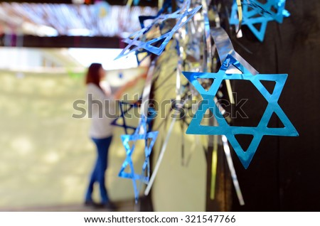 Jewish woman decorating here family Sukkah for the Jewish festival of Sukkot. A Sukkah is a temporary structure where meals are taken for the week. - stock photo